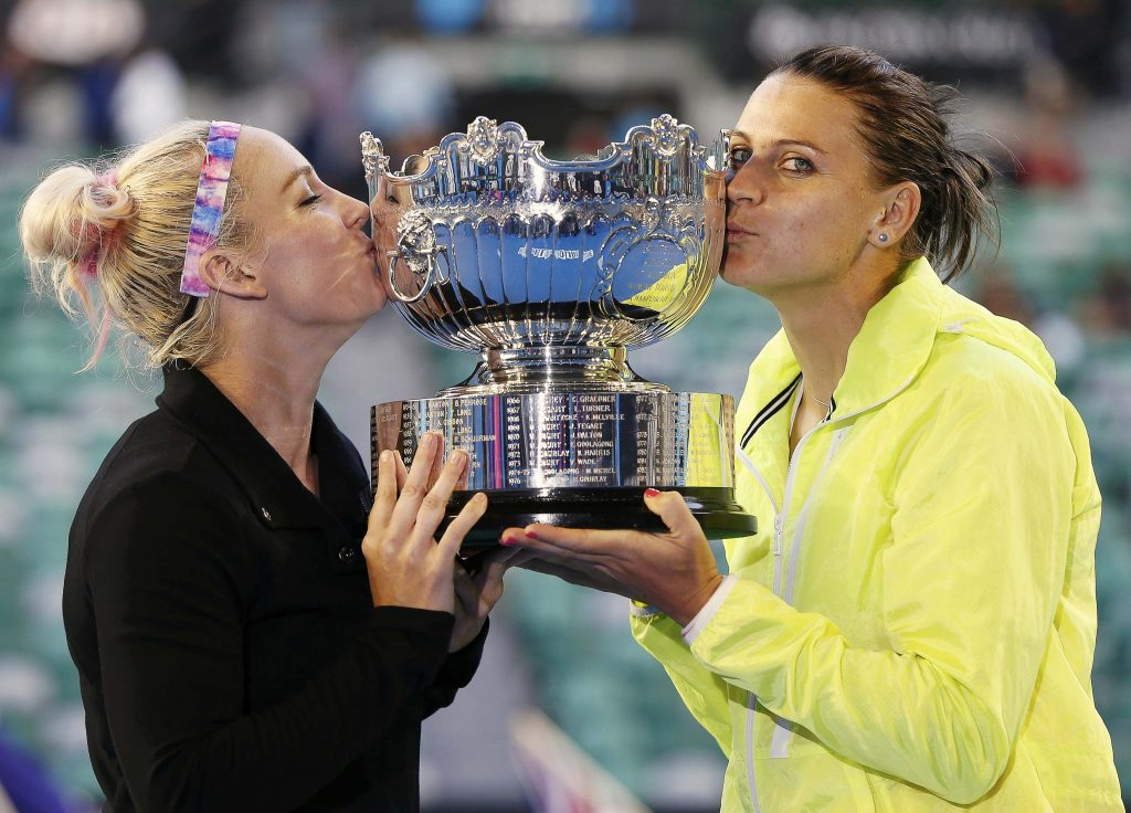 Bethanie Mattek-Sands (L) of the U.S. and Lucie Safarova (R) of Czech Republic kiss their trophy after winning their women's doubles final match against Zheng Jie of China and Chan Yung-Jan of Taiwan at the Australian Open tennis tournament in Melbourne January 30, 2015. REUTERS/Issei Kato (AUSTRALIA - Tags: SPORT TENNIS)